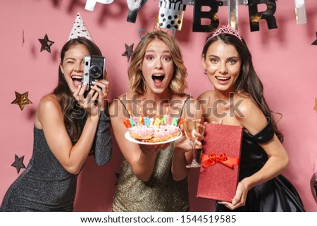 Image of excited party girls with retro camera holding birthday cake and gift box isolated over pink background
