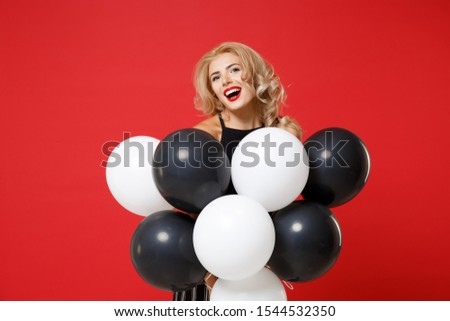 Laughing young woman girl in black clothes posing isolated on bright red wall background. International Women's Day birthday holiday party concept. Mock up copy space. Celebrating hold air balloons #1544532350