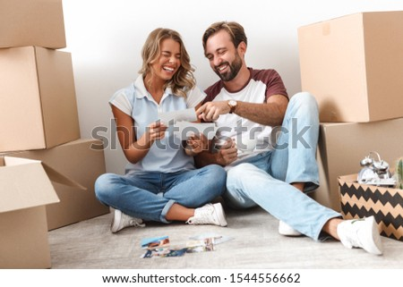 Happy lovely couple moving to a new flat, sitting on a floor surrounded with boxes, looking through old photos #1544556662