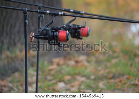 Fishing rods on holder, reels with red line #1544569415