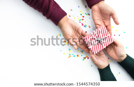 Celebration party and anniversary concepts ideas with young person hand giving gift box decoration with colorful confetti,paper art on white color background.copy space #1544574350