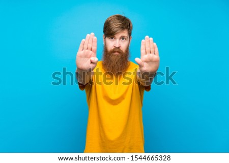 Redhead man with long beard over isolated blue background making stop gesture and disappointed #1544665328