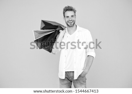 Consumerism concept. Big discount. Great choices great purchases. Happy man holding purchases in paper bags. Cheerful client customer consumer smiling with fashion purchases. Impulse purchases. #1544667413