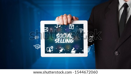 Young business person working on tablet and shows the inscription: SOCIAL SELLING #1544672060