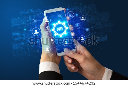 Female hand holding smartphone with IVR abbreviation, modern technology concept #1544674232