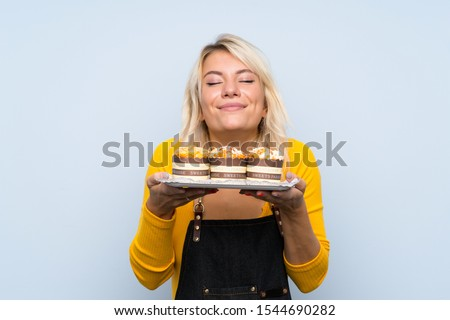Young blonde woman over isolated background holding mini cakes enjoying the smell of them #1544690282