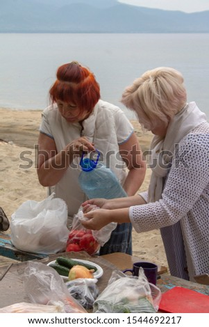 Girlfriends prepare the ingredients for the preparation of barbecue on the shore of Lake Baikal #1544692217