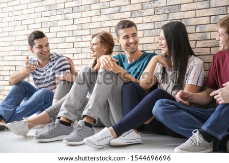 People sitting together near brick wall. Unity concept #1544696696