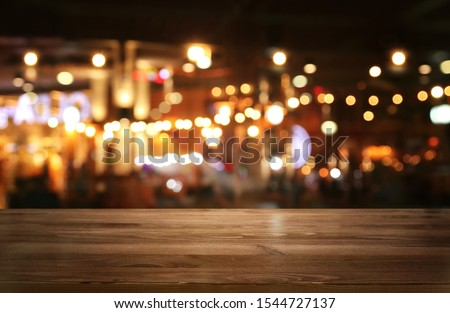 background Image of wooden table in front of abstract blurred restaurant lights #1544727137
