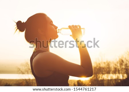 Beautiful girl in sportswear drinks water from a bottle at sunset Royalty-Free Stock Photo #1544761217