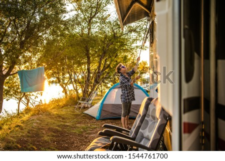 Caucasian Retired Woman in Her 60s Extending RV Awning at RV Park Campsite. Summer Vacation Time with Recreational Vehicle.  #1544761700