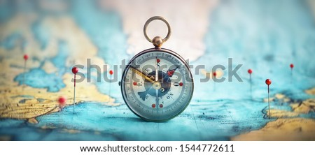 Magnetic compass  and location marking with a pin on routes on world map. Adventure, discovery, navigation, communication, logistics, geography, transport and travel theme concept background. Royalty-Free Stock Photo #1544772611