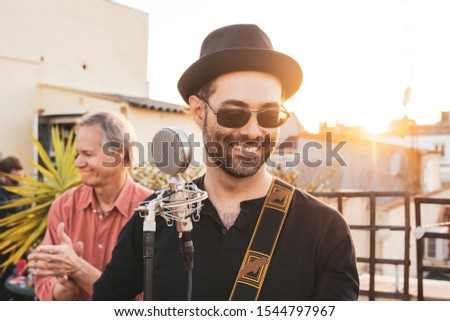 Man in adult age performing on a rooftop at summer season. Music live concerts concept. Lead singer of a rock band singing a song. Portrait of a hipster male musician playing on an intimate concert. #1544797967