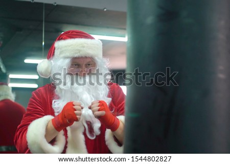 Santa Claus Fighter kickbox With Red Bandages boxer hitting a huge punching bag at a boxing studio. Santa Claus boxer training hard. Royalty-Free Stock Photo #1544802827