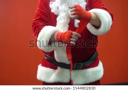Santa Claus Fighter kickbox With Red Bandages against the background of a red wall Royalty-Free Stock Photo #1544802830