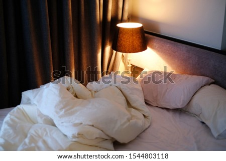 classic bedroom style with set of pillows on bed and classic lamp in white color tone, unmade bed inside of a hotel room, coziness, comfort, interior and holidays concept #1544803118