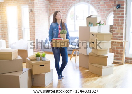 Beautiful asian young woman holding boxes, smiling happy moving to a new home #1544831327