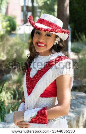 Young and beautiful Hispanic high school girl in her school dance uniform posing for school pictures