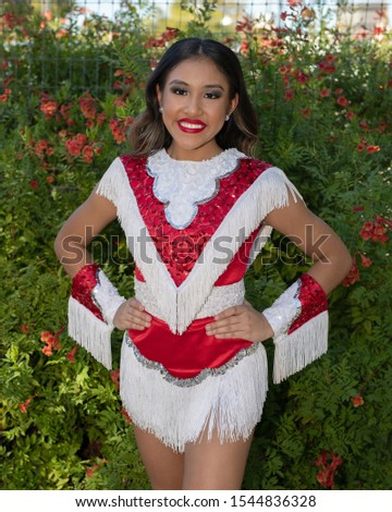 Young and beautiful Hispanic high school girl in her school dance uniform posing for school pictures