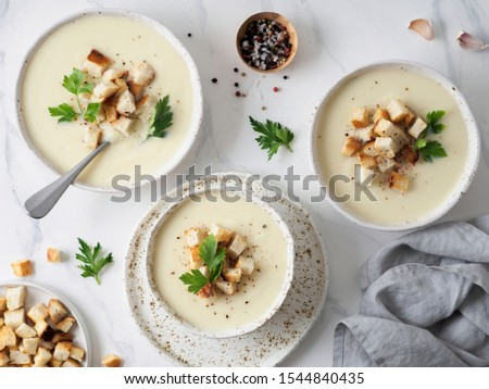 cauliflower potato soup puree on white marble tabletop, Creamy cauliflower soup with toasted bread croutons. Vegetarian healthy food concept. Ideas and recipes for winter meal. Top view or flat lay #1544840435