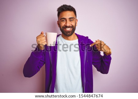 Indian man wearing purple sweatshirt drinking cup of coffee over isolated pink background with surprise face pointing finger to himself #1544847674
