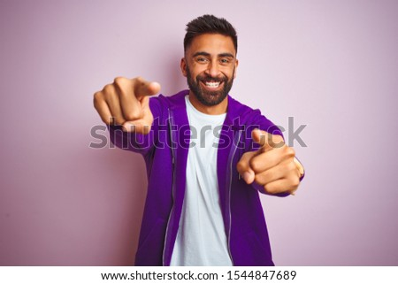 Young indian man wearing purple sweatshirt standing over isolated pink background pointing to you and the camera with fingers, smiling positive and cheerful #1544847689