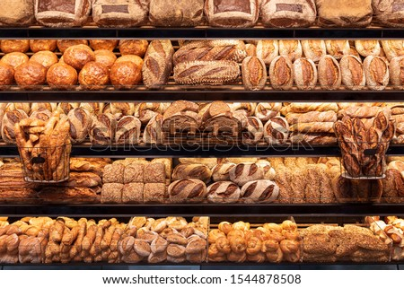 Delicious loaves of bread in a german baker shop. Different types of bread loaves on bakery shelves. #1544878508