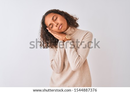 Young brazilian woman wearing turtleneck sweater standing over isolated white background sleeping tired dreaming and posing with hands together while smiling with closed eyes. #1544887376