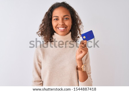 Young brazilian woman holding credit card standing over isolated white background with a happy face standing and smiling with a confident smile showing teeth