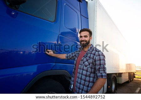 Truck driver occupation. Middle aged bearded trucker standing by his semi truck vehicle ready for work. Transporting and delivering goods. Transportation services. #1544892752
