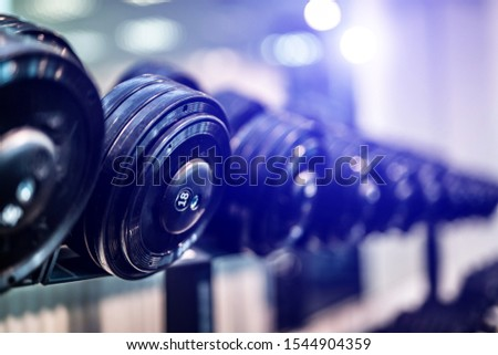 Rows of dumbbells in the gym with blurred background. Closeup. Sport equipment. Healthy life concept. #1544904359