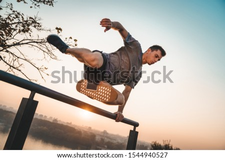Athlete jumping over a wall. Free running parkour - Stock photo
