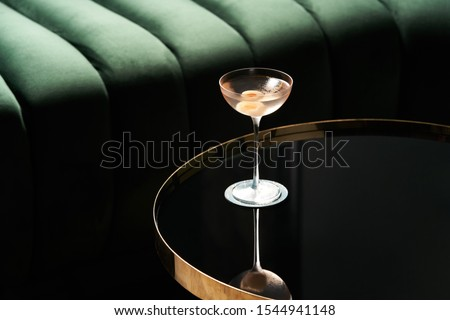 Classic cocktail glass on glass table in night club restaurant. Alcohol cocktail drink, close-up. Modern alcoholic beverage #1544941148