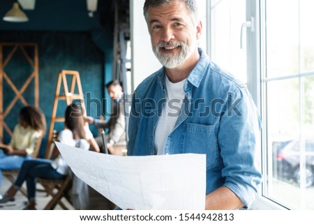 Portrait of a casually dressed mature businessman smiling confidently while working with documents in a modern office #1544942813