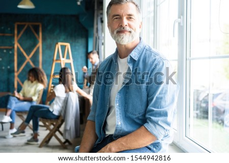 Portrait of a casually dressed mature businessman smiling confidently while working with documents in a modern office #1544942816