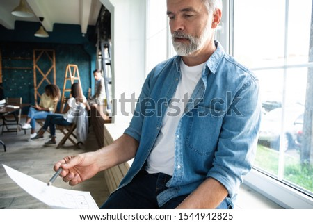 Portrait of a casually dressed mature businessman smiling confidently while working with documents in a modern office #1544942825