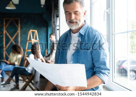 Portrait of a casually dressed mature businessman smiling confidently while working with documents in a modern office #1544942834