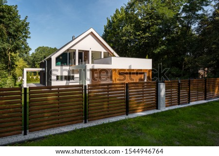 Spacious white house with wooden decoration on garage and wood style fence Royalty-Free Stock Photo #1544946764