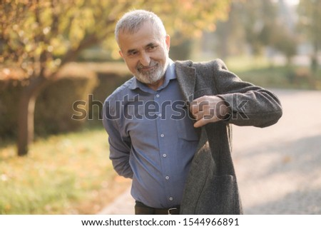 Handsome elderly man putting on a gray jacket. Old gray-haired bearded man walk in the autumn park. Yellow background #1544966891