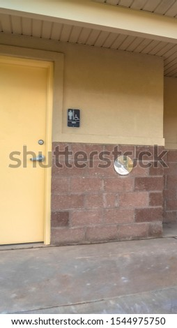 Vertical frame Public restroom at a golf course with white doors and concerete and brick wall #1544975750