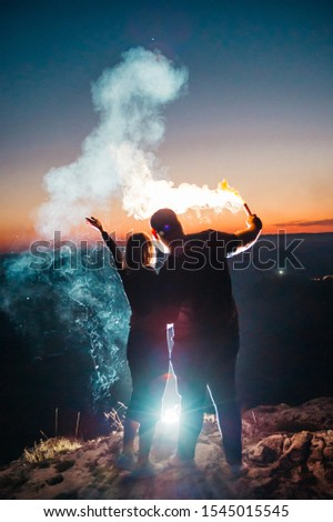 couple and yellow smoke grenade on the background of the city lights. evening night time on the top of the hill #1545015545