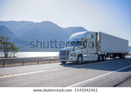 Professional grade big rig semi truck with chrome accessories transporting frozen cargo in refrigerated semi trailer moving on the road along river with bewitching view on the opposite bank #1545042461