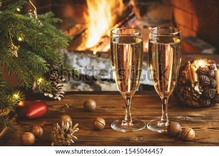 Christmas composition - Two glasses with champagne on a wooden table near a Christmas tree in a room with a burning fireplace
