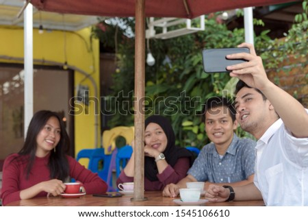 Multiracial group of four asian friends having a coffee together. Two women and two men at cafe, talking, laughing and enjoying their time while taking group selfie. #1545106610