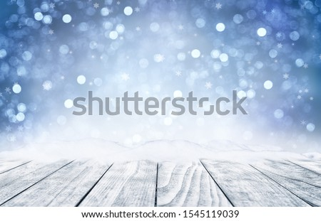 Decorative Christmas background with bokeh lights, snowflakes and empty old wooden table. Christmas and Happy New Year blue background with snowflake. Winter landscape with falling snow. #1545119039