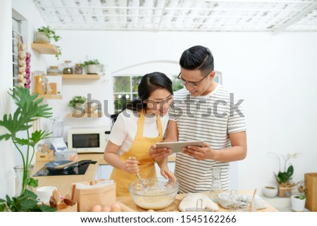 Young asian man and woman together cooking cake and bread with egg, looking menu from tablet in the flour happy relaxing in at home #1545162266