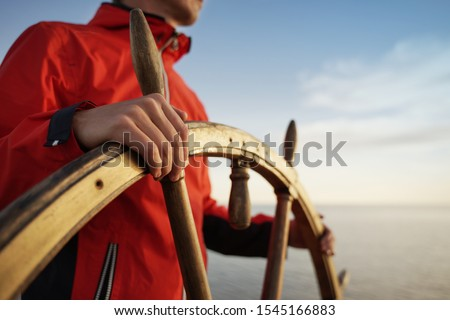 Man Holding Hands on ship rudder and navigates.  Royalty-Free Stock Photo #1545166883