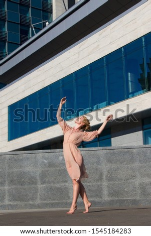 Ballerina in light dresses dancing on a street background of a modern glass building business center #1545184283