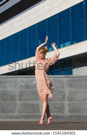 Ballerina in light dresses dancing on a street background of a modern glass building business center #1545184301