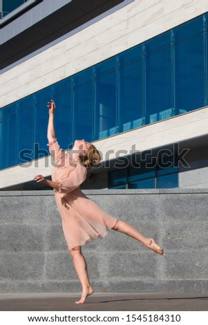 Ballerina in light dresses dancing on a street background of a modern glass building business center #1545184310